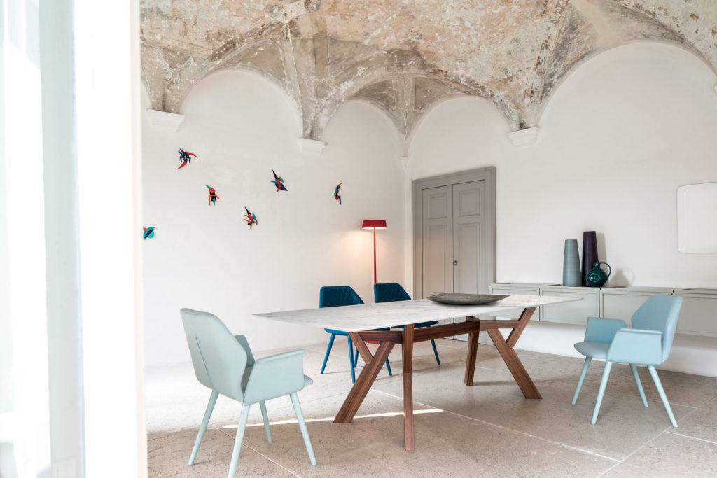 Table de réception Trigono avec piètement en bois teinté et plateau en marbre – Chaise design AVA colori bleu ciel Bross (profil)