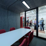 Framery-Smart-Office-Acoustic-Four-Person-Meeting-Pod-with-Red-Chairs-and-Conference-Table